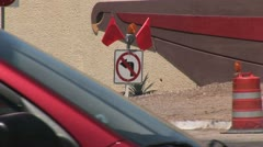 """View of """"No Left Turn"""" Traffic Control Sign and Safety Barrels As Traffic Passes Stock Footage"""