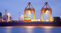 Stock Photo of cargo ship in port at dusk