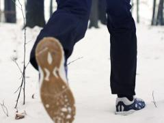 Jogger running through deep snow in forest NTSC - stock footage