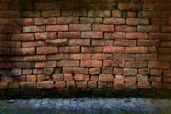 dirty grunge red stone brick wall with pavement - stock photo