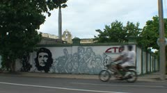 Cienfuegos, Che Guevara on billboard, woman passing by Stock Footage