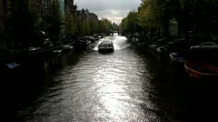 Stock Video Footage of Amsterdam Canals, Holland with Boats & Boat driving under Bridge