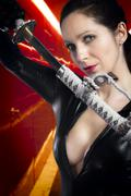 Anime stylized sexy brunette with holding a katana sword with two hands. Stock Photos
