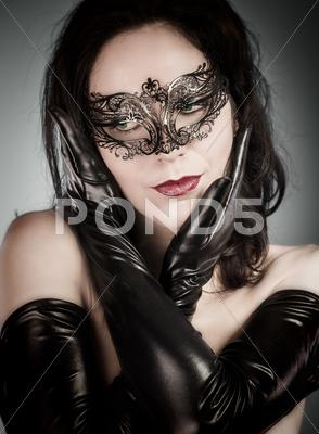 Stock photo of venetian mask. a pretty retro girl in black wearing a cute hat and a scarf.