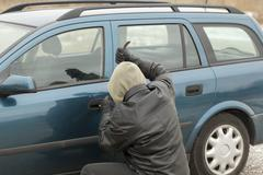 Robber with a crowbar trying to open the car door - stock photo