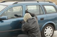 Stock Photo of Robber with a crowbar trying to open the car door