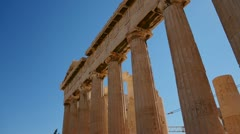 Low angle pan of the columns of the Acropolis and Parthenon on the hilltop in Stock Footage
