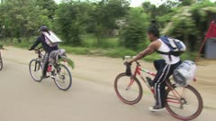 In Motion View of Bicycle Riders With Portraits of Christ On Their Backs 2 Stock Footage