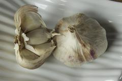 One whole and one halved garlic, variegated, on ridged white dish Stock Photos