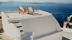 Pan across deck chairs sit on a beautiful balcony in the Greek Islands. Stock Footage