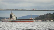 Transportation concept with a cargo ship sailing under busy bridge Stock Footage