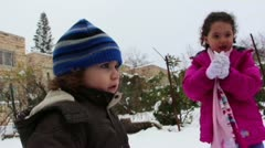 Kids play in the snow building snowman Stock Footage
