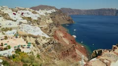 Slow pan of white houses lining the hillsides of the Greek Island of Santorini - stock footage