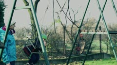 Little boy with sister swinging in autumn playground, slow motion shot at 240fps Stock Footage