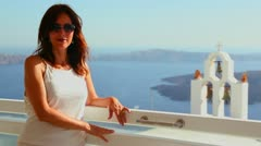 A woman stands before a church on the Greek Island of Santorini. - stock footage