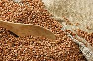 Buckwheat groats and wooden spoon Stock Photos