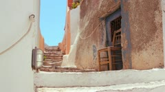 Chairs sit in a white and brown alley on the island of Santorini in Greece. Stock Footage
