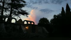 Clouds moving at sunrise, roman ruins and trees in silhouette - stock footage
