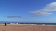 An empty beach with a lone garbage can and blue sky. - stock footage