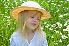 shy little girl in daisy field - stock photo