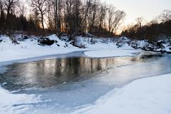 snow riverbank of forest stream in winter - stock photo