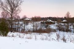 pink winter sunset under rustic houses - stock photo