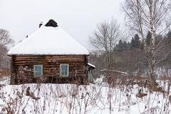 snow covered wooden rustic house - stock photo