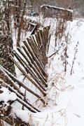 backyard rickety fence in winter - stock photo