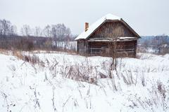 abandoned house in snow-covered village - stock photo