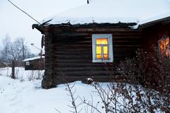yellow lighting window of rural house - stock photo