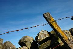 Dry stone wall and barbed wire - stock photo