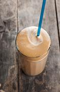 cold frappe drink on a wooden table - stock photo