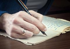 Woman hand writes on a paper Stock Photos