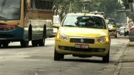 Stock Video Footage of Street Level View Of A Waiting Taxi As Heavy Traffic Zooms By