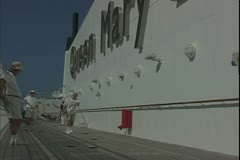 The Queen Mary 2, ocean liner, shuffleboard on the top deck, players Stock Footage