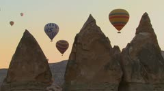 Three hot air balloons are beautifully silhouetted against a mountain peak in Stock Footage
