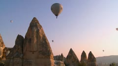 Hot air balloons fly over the magnificent geological formations of Cappadocia, - stock footage