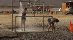 Asian weman put mud and shower at dead sea nature spa Stock Footage