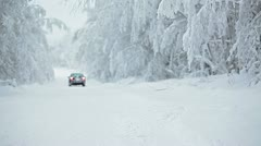 Car on snowy road reversing to camera Stock Footage
