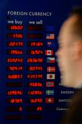 Man rushing past a currency board - stock photo