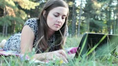 girl working at a laptop in the park - stock footage