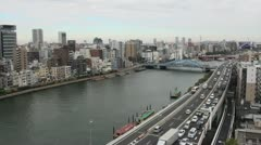 Gridlock and traffic jam during rush hour with Tokyo skyline in background - stock footage