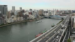 Congested ring road, skyline, tourist boat, river, in Asakusa district, Tokyo Stock Footage