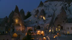 Strange dwellings built into a hillside at dusk or night in Cappadocia, Turkey. - stock footage