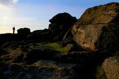 Climber Standing on Rocks on Dartmoor - Silhouette, Beautiful Sky - stock photo