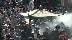 Crowds gather around urn that burns incense in Tokyo, Japan Stock Footage