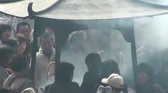 Incense burning urn and crowd gathering at Sensoji temple complex in Tokyo Stock Footage