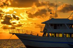 Boat and Golden Sunrise Stock Photos