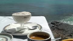 Vanilla ice cream in bowl and a cup of coffee on sea background  Stock Footage