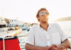komea nuori mies lomalla auringonlaskun - stock photo